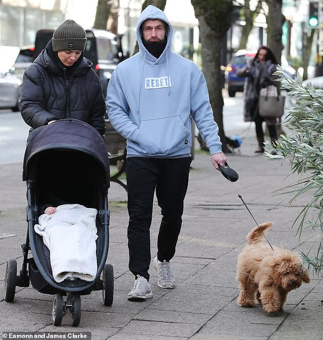 Sweet:The actor, 36, cut a casual figure as he pushed Milo in a pram while Liz walked their adorable Cockapoo puppy