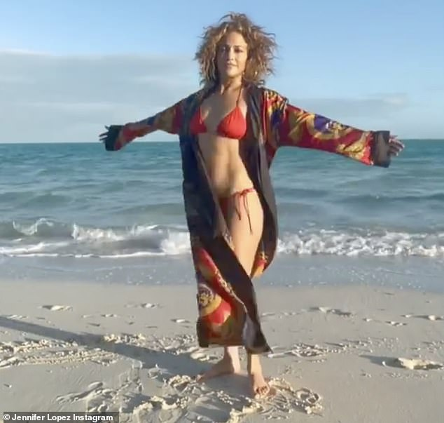 Not bad:The 51-year-old dancer, actress and singer posed in a bright red bikini while on a Florida beach, showing off her toned tummy and shapely legs, in a new video