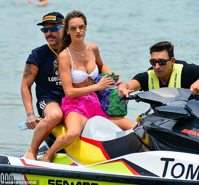 Fun in the sun: Ambrosio showed off her impressive physique as she went for a jet ski trip with a male friend behind her