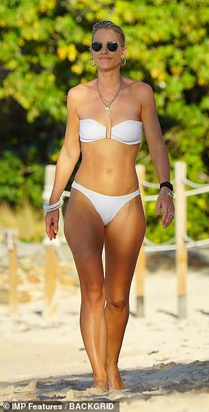 Radiant: The white bikini highlighted Vogue's glowing tan, while she accessorised her beach look with a selection of bangles, gold chain necklaces and hoop earrings