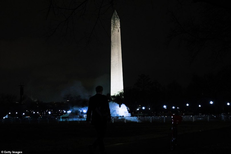 A man is seen standing in front of the Washington Monument as Trump supporters protested