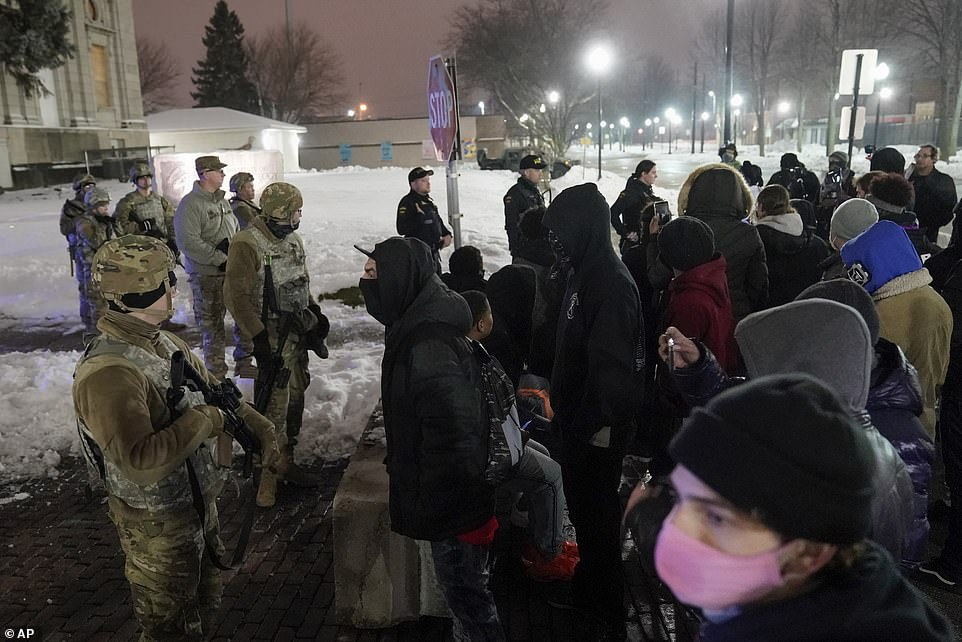 A small crowd of peaceful demonstrators gathered in Kenosha Tuesday night protesting against the DA's decision and were seen chanting 'hands up don't shoot' in front of National Guard members
