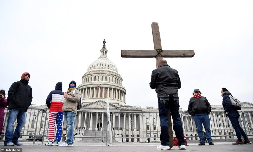 Jeremy LaPointe of Lumberton, Texas, holds a cross as he joins supporters of Trump gathered outside the US Capitol where Congress will meet to certify the electoral college vote for President-elect Joe Biden in Washington, DC, on Wednesday