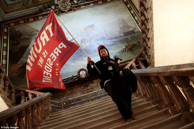 A rioter holds a Trump flag inside the US Capitol after storming the building