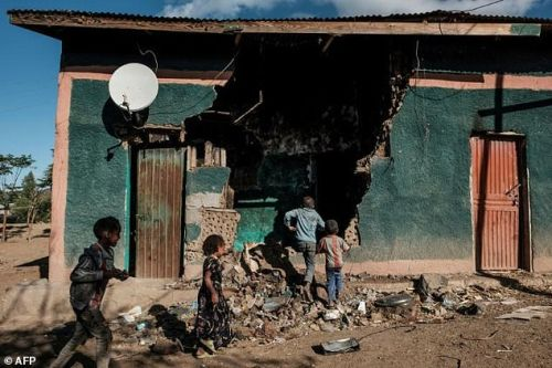 Children play in front of a house that was damaged during the fightings that broke out in Ethiopia's Tigray region, in the village of Bisober, on December 9, 2020