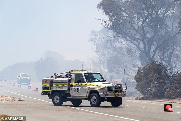 Emergency vehicles drive through smoke on Patterson Road in Kwinana, as bushfires continue burn in the north and soutbh of Perth (pictured)