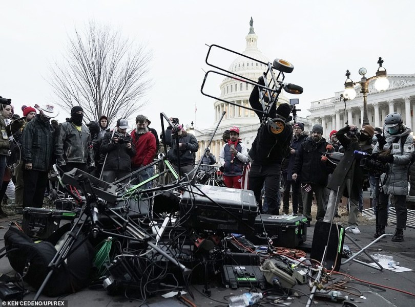A vandal is seen destroying the equipment in scenes of chaos in Washington DC on Wednesday