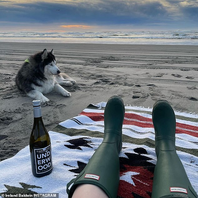 Chilling out: It flashed a cute grin from the back of their pick up truck before finding a spot on the sand next to her while she worked on a bottle of wine