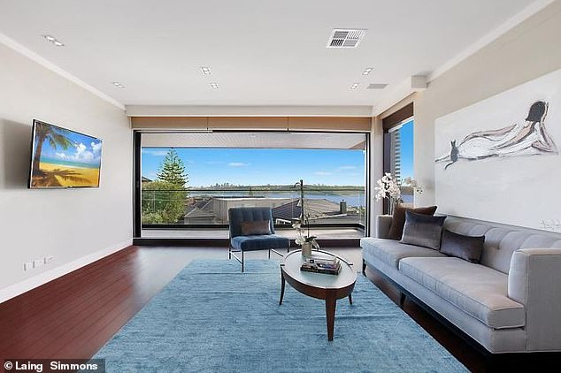 What a view: The couple's home has a spacious living area with ceiling to floor windows that look out to the harbour
