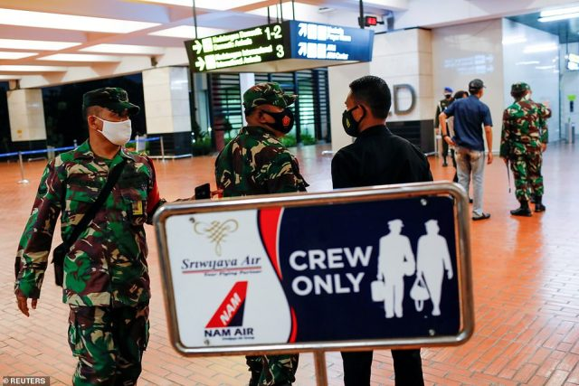 Indonesian soldiers are seen at Soekarno-Hatta International Airport in Jakarta after the Sriwijaya Air plane vanished over the ocean