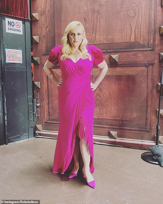 Shrinking star: Rebel Wilson showed off her trim figure in a pink Badgley Mischka frock on set, in photos shared to Instagram on Saturday, after her incredible 30 kilogram weight loss