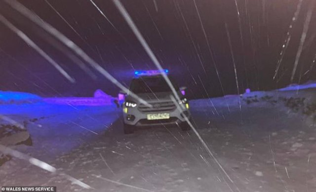 All car parks in Snowdonia National Park have now been closed to visitors. Pictured is a police car patrolling the beauty spot last night