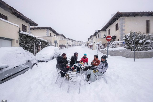 With such high snowfall a rarity in Spain, people took to the streets to enjoy the snow. This group of neighbours sit around a table in the middle of a street in Bustarvejo, on the outskirts of Madrid