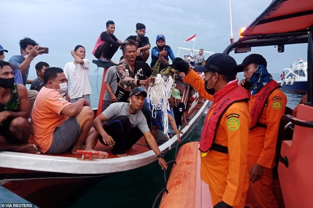 Local fishermen and rescuers hold suspected remains of the Sriwijaya Air plane flight SJ182, which crashed into the sea near Jakarta, Indonesia, January 9