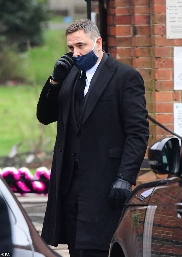 Emotional: David was pictured wiping away a tear as he attended the funeral
