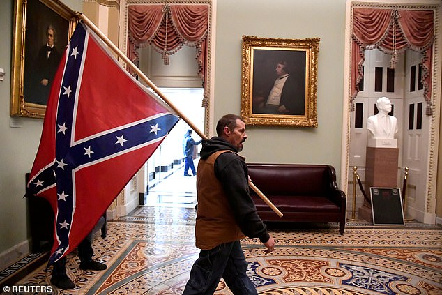 A supporter of Donald Trump carries a Confederate flag on the second floor of the US Capitol
