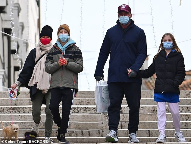 Sweet: Their son Kai bundled up for the chilly weather in a green winter jacket and Adidas trousers while their daughter was seen holding her father's hand as she wore a black coat