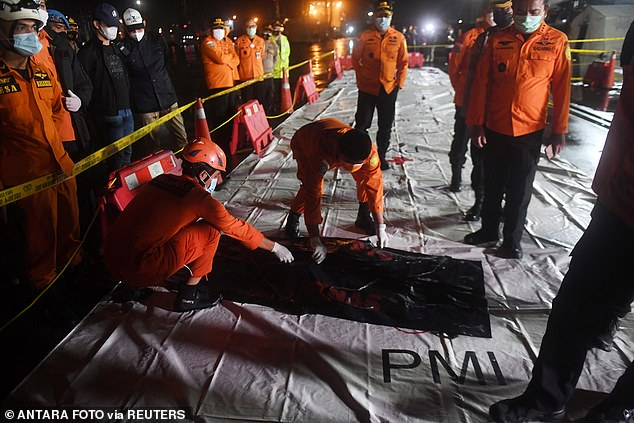 Indonesian rescue members check a body bag as a huge team continues their search to find wreckage and passengers