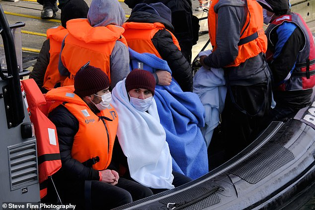 A group of migrants are brought ashore by Border Force Officials in Dover after they are spotted along the English Channel