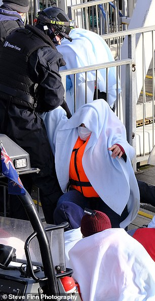 A migrant is brought ashore