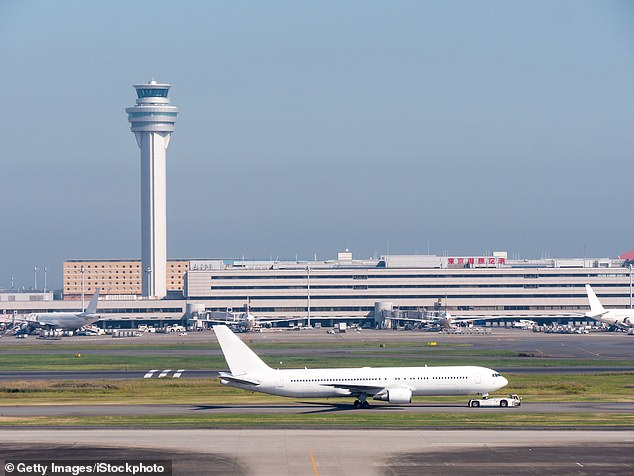Three of those who tested positive for the virus exhibited symptoms such as difficulty breathing, fever and a sore throat.  Pictured: Haneda Airport in Tokyo