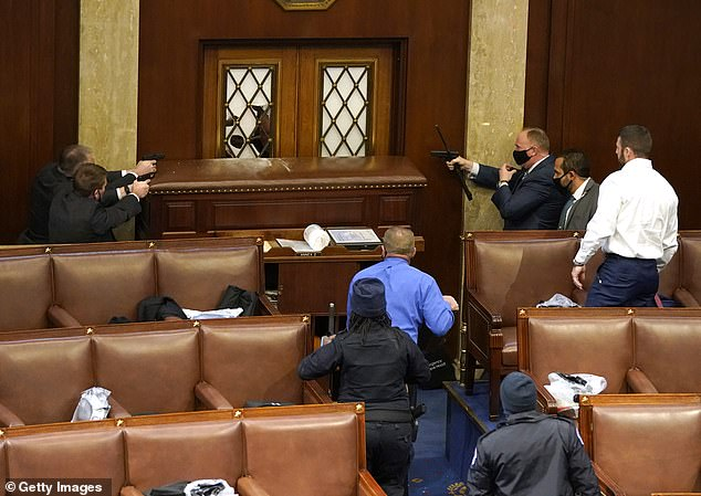 Capitol Police officers point their guns at a door that was vandalized in the House Hall during a joint session of Congress