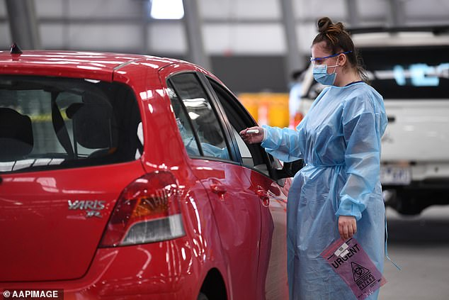 Pictured: Healthcare workers are seen attending to people at a drive through covid-19 testing facility at the Royal Melbourne Showgrounds in Melbourne on January 4