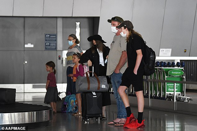 Pictured: a family at baggage collection area after arriving on Qantas flight from Brisbane at Tullamarine Airport in Melbourne on January 8