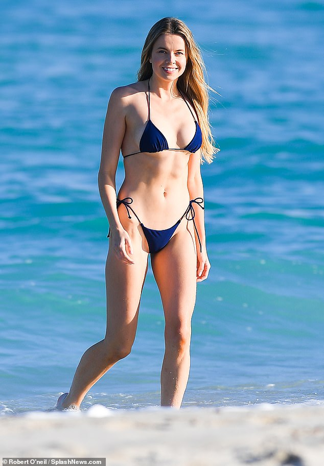 Toned: The model, 28, sizzled as she ran along the sand and showcased her athletic physique in a string thong bikini