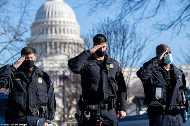 Police officers salute as a hearse carrying the body of Officer Brian D. Sicknick, who was killed by rioters Wednesday, passes members of the Capitol and Metropolitan police during a procession on Third Street on Sunday