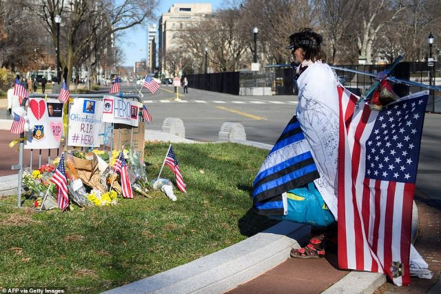 People pay their respects at a memorial for fallen police officer, Brian Sicknick who was reportedly struck in the head with a fire extinguisher on Wednesday while struggling with the rioters who swarmed through the halls of Congress