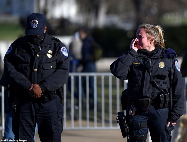 One police officer, right, was unable to hold many tears as the cortege made its way by. Another officer looked down