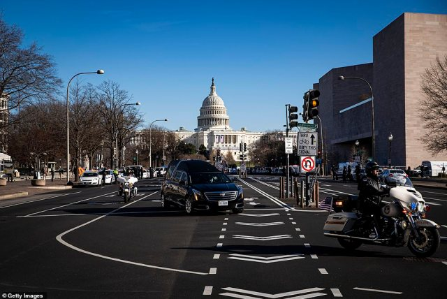 A hearse carrying the casket of Brian Sicknick turns onto Constitution Avenue during a police procession on Sunday