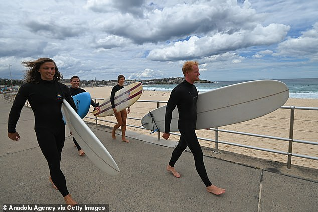 Surfers from the South Bondi Surf Club and the Surry Hills Sluzzas prepare to enter the water at Bondi Beach in December