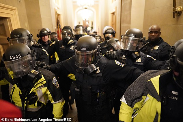 Riot police clear the hallway inside the Capitol on Wednesday, Jan 6, 2021 in Washington, DC