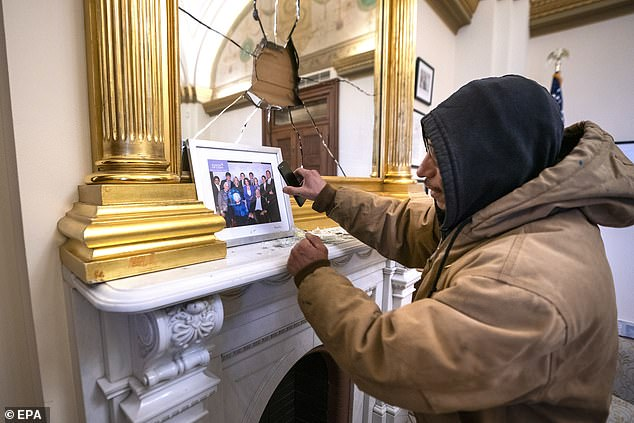 One man is seen photographing a picture from Pelosi's office, having broken into the room