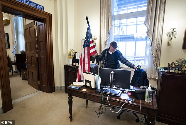 Barnett is pictured inside Pelosi's office on Wednesday, having stormed into the Capitol