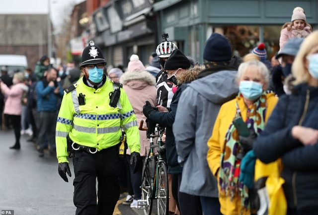 In Liverpool, police were pictured looking on as football supporters who had gathered outside the Marine v Spurs FA Cup blatantly ignored social distancing rules