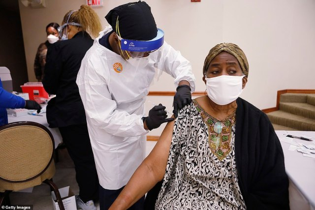 A healthcare worker administers the COVID-19 vaccine to a resident living in the Jackson Heights neighborhood at St. Johns Missionary Baptist Church on Sunday in Tampa, Florida