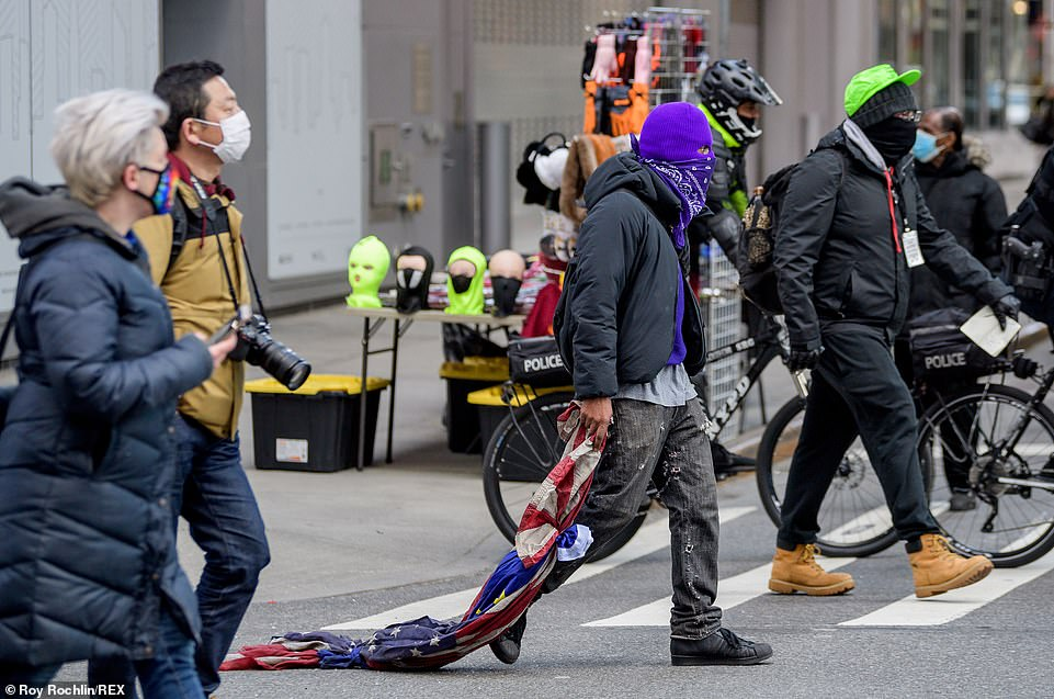 Protest: A man wearing a purple ski mask dragged an American flag over a pedestrian crossing during Sunday's march