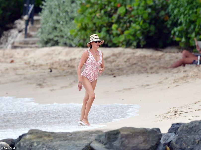 Wow: Lauren kept cool in the sizzling temperatures in a chic wide-brimmed hat and shades, and finished her beach glam look with statement necklaces