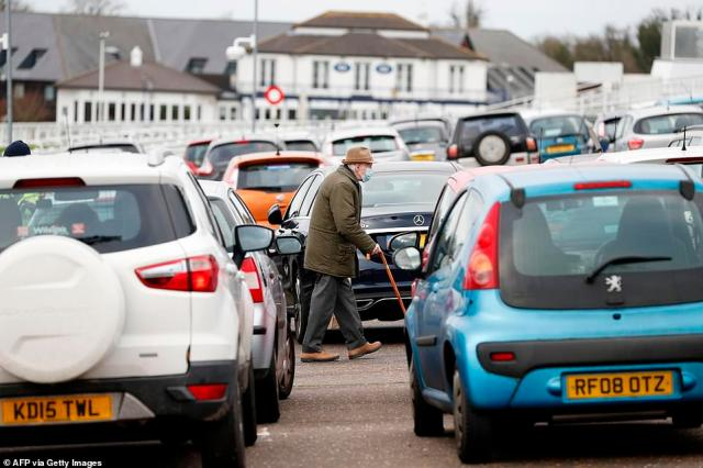An elderly man walks through the packed car park at Epsom racecourse in Surrey as vaccinations stepped up