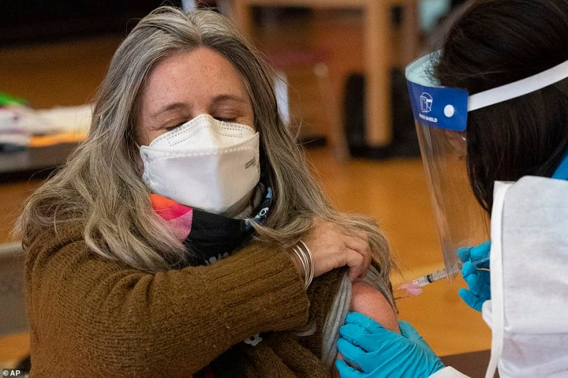A New York City school teacher is seen receiving her first dose of the vaccine on Monday