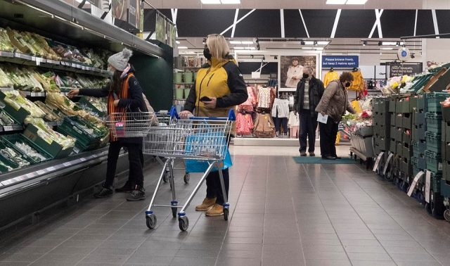 Customers wearing face coverings on the vegetable aisle at a Tesco Extra store in south-east London early this morning