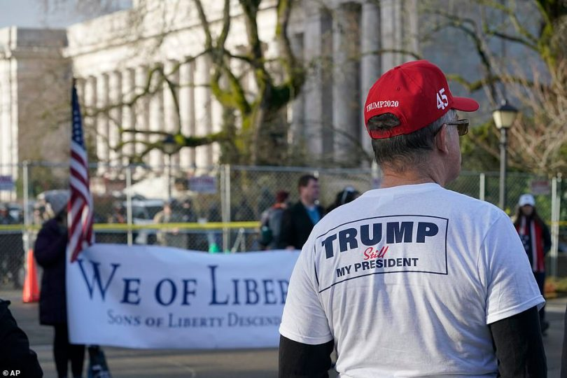 A supporter of President Donald Trump listens to speakers during a rally outside the state capitol in Washington over the weekend. He wears a t-shirt which says: 'Trump still my president'