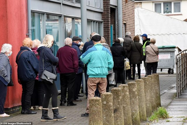 People queue outside Hornchurch library in the London Borough of Havering for their Covid-19 vaccination today