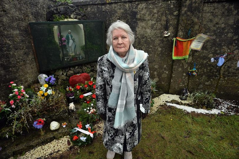 Survivor Carmel Larkin from Tuam who was born at the notorious Mother and Baby Home in County Galway stands beside flowers laid to the victims yesterday. Ms Larkin said: 'Well it's our holocaust isn't it? They had the holocaust in Germany but the mother and baby homes were our holocaust'