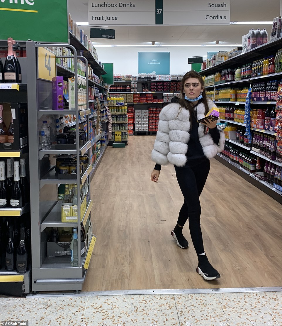 Cover-up in Aisle Three: Shopper at Morrisons in Thamesmead has brought along her face mask – but failed to utilise it correctly