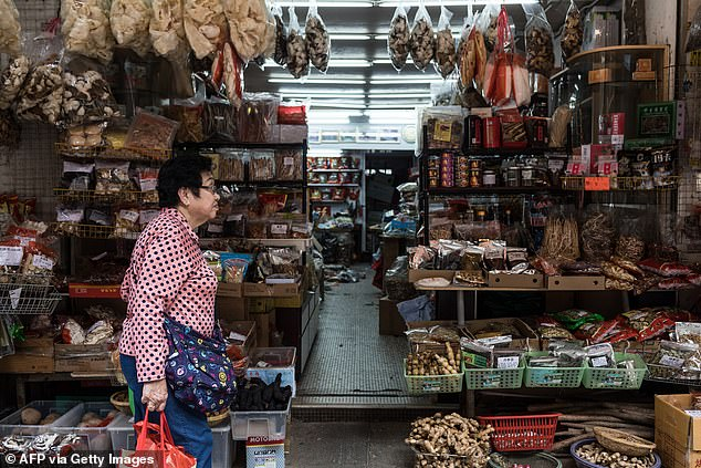 Pictured: A woman walks past a shop on a street selling deep-fried scales of endangered pangolins, or scaly anteaters, in Hong Kong despite being the subject of an international ban