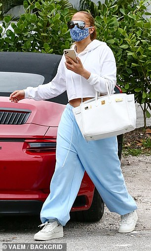 JLo wore her long hair tied back into a ponytail and carried a large white leather purse